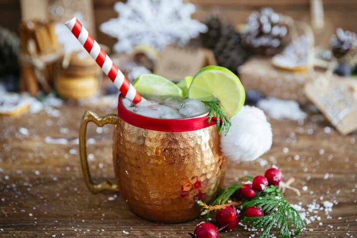 a christmas cocktail moscow mule is shown with a festive wooden background