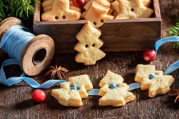three Christmas tree butter cookies are strung together by a blue ribbon